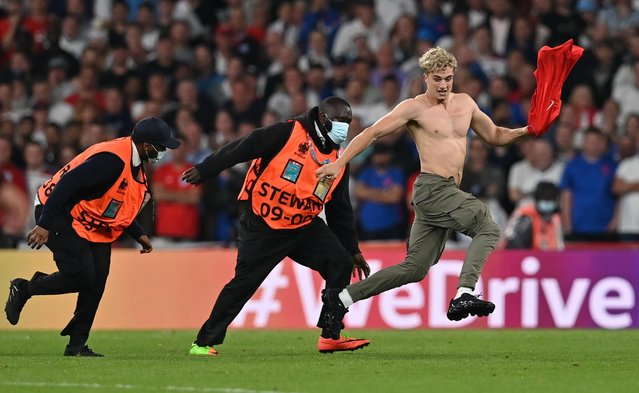 Fan invades the pitch during the match Italy v England as stewards attempt to tackle him at Wembley Stadium in London, Britain on July 11, 2021. (Photo by Paul Ellis/Reuters)