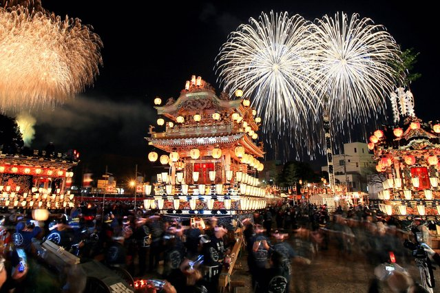 Fireworks explode above the illuminated floats during the Chichibu Yomatsuri, or Chichibu Night Festival on December 3, 2013 in Chichibu, Saitama, Japan. 194,000 visitors enjoy the annual festival. (Photo by The Asahi Shimbun via Getty Images)