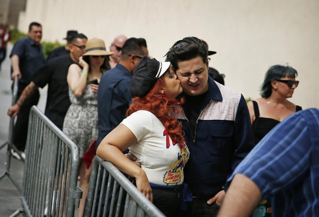 In this April 5, 2015, photo, Angie Almilla kisses Eric Martinez while waiting in line for a pool party at the Viva Las Vegas Rockabilly Weekend in Las Vegas. The event included fashion shows, dance lessons and contests set against a backdrop of rock 'n' roll and pre-1963 classic cars. (Photo by John Locher/AP Photo)