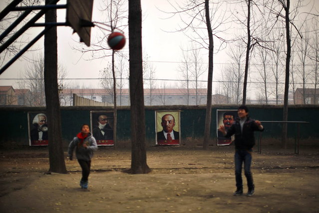 Students play basketball next to portraits of German philosophers Karl Marx and Friedrich Engels and Soviet leaders Vladimir Lenin and Joseph Stalin (L-R) at the Democracy Elementary and Middle School in Sitong town,  Henan province December 3, 2013. (Photo by Carlos Barria/Reuters)