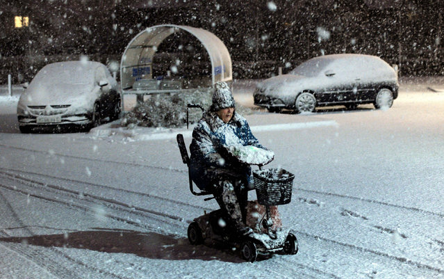 A woman makes her way through the snow on a mobility scooter in Filey on the North east coast of England Friday January 13, 2017, as Scotland and the North of England were covered in a blanket of snow. (Photo by John Giles, PA Wire via AP Photo)