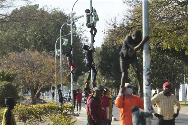 Supporters of Zambian opposition leader Hakainde Hichilema remove campaign posters of Zambian President Edgar Lungu from street poles in Lusaka, Zambia, Monday August 16, 2021. Hichilema has won the southern African country's presidency after taking more than 50% of the vote. (Photo by Tsvangirayi Mukwazhi/AP Photo)