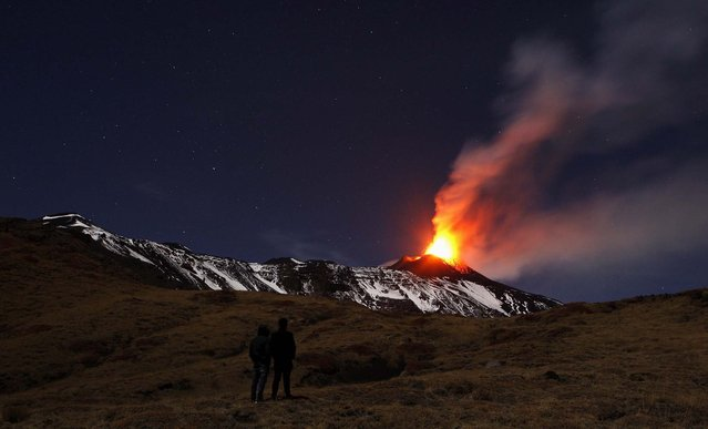 People watch Italy's Mount Etna, Europe's tallest and most active volcano, spewing lava as it erupts on the southern island of Sicily, November 17, 2013. (Photo by Antonio Parrinello/Reuters)