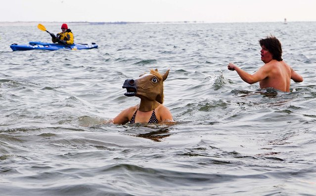 Swimmers, some in unusual costume, swim in the frigid waters at Coney Island beach in New York as they take part in the 111th annual New Year's Day Polar Bear Plunge. (Photo by Craig Ruttle/Associated Press)
