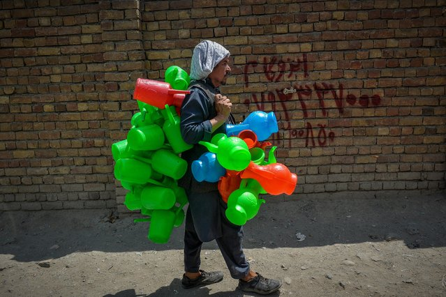 A hawker selling plastic containers walks along a street at a market area in Kabul on August 23, 2021 following the Taliban's military takeover of the country. (Photo by Hoshang Hashimi/AFP Photo)