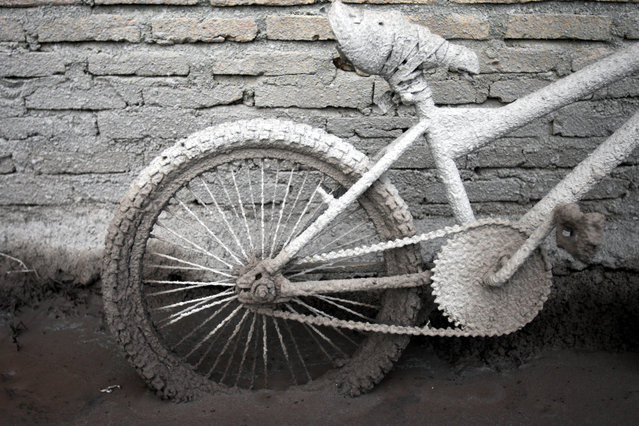 A bicycle is caked with volcanic ash from the eruption of Mount Sinabung outside a house in Sibintun, North Sumatra, Indonesia, Tuesday, January 7, 2014. (Photo by Binsar Bakkara/AP Photo)