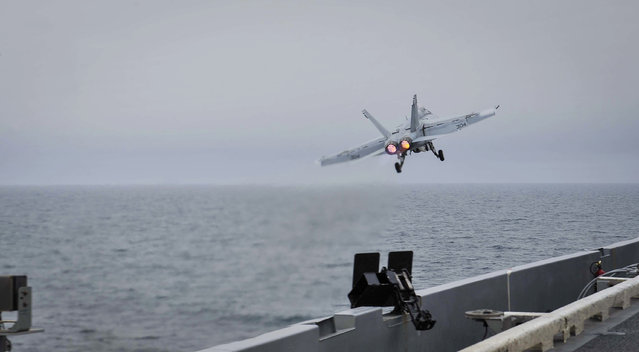 In this Wednesday, April 15, 2015 image released by U.S. Navy Media Content Services, an F/A-18E Super Hornet, assigned to the Knighthawks of Strike Fighter Attack Squadron 136, launches off the flight deck aboard Nimitz-class aircraft carrier USS Theodore Roosevelt in the Fifth Fleet area of operations. (Photo by Mass Communication Specialist Seaman Anna Van Nuys/U.S. Navy Media Content Services via AP Photo)