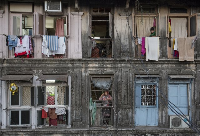 Residents look out of windows of an apartment in Mumbai March 15, 2015. The cost for buying a 200 square feet (18 square meters) one-bedroom apartment in this building is around 25,000 Indian rupees per square feet ($ 400) or 5,000,000 Indian rupees ($ 80,000). The rent for an apartment in the same building is around 12,000 Indian rupees ($ 190) per month. (Photo by Danish Siddiqui/Reuters)