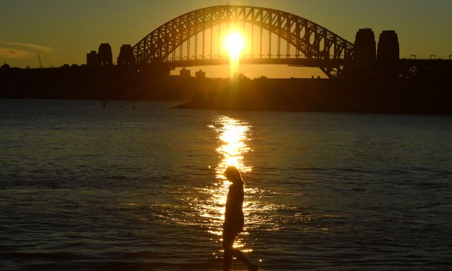 A woman walks past the Sydney Harbour Bridge at dawn in Sydney, Sunday, November 8, 2020. (Photo by Mick Tsikas/AAP Image)