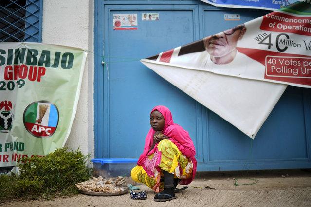 A Nigerian woman sells peanuts outside Incumbent President Muhammadu Buhari's campaign headquarters in Abuja, Nigeria, Tuesday February 26, 2019. (Photo by Jerome Delay/AP Photo)