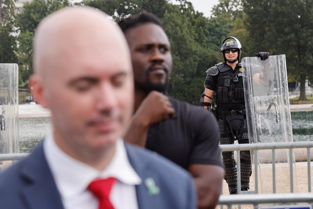 A police officer reacts while standing behind Matt Braynard, Executive Director of Look Ahead America, during a rally in support of defendants being prosecuted in the January 6 attack on the U.S. Capitol, in Washington, D.C., U.S., September 18, 2021. (Photo by Jonathan Ernst/Reuters)