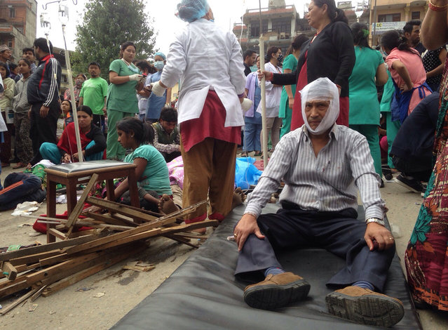 Injured people receive treatment outside the Medicare Hospital in Kathmandu, Nepal, Saturday, April 25, 2015. (Photo by Niranjan Shrestha/AP Photo)