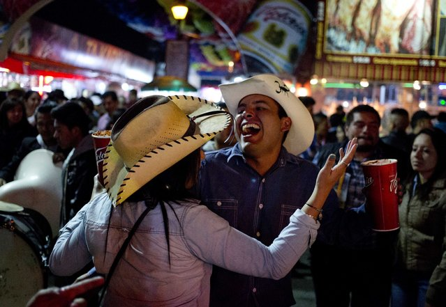In this April 10, 2015 photo, a couple, holding michelada drinks, dances to the rhythm of a Mexican Norteño band at the Texcoco Fair on the outskirts of Mexico City. Sometimes the trumpets and tubas of the roving brassy groups clash with each other as the play songs for about $15 each. (Photo by Eduardo Verdugo/AP Photo)