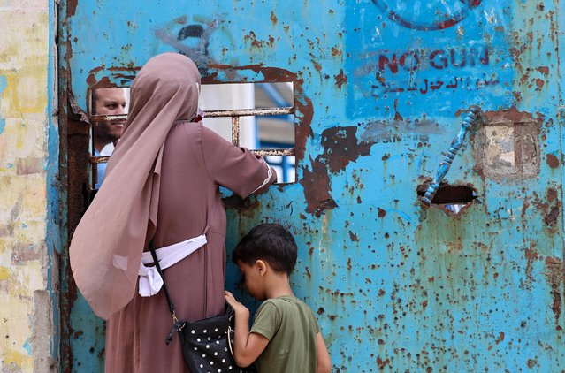 A Palestinian woman and her child stand next to a window of an aid distribution centre run by the United Nations Relief and Works Agency (UNRWA) in Gaza City, on September 16, 2021. (Photo by Mohammed Abed/AFP Photo)