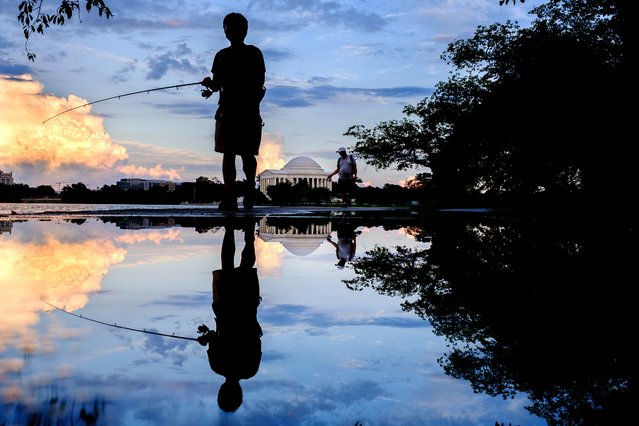 Fisherman are reflected in rain puddles as they walk along the edge of the Tidal Basin near the Jefferson Memorial after an afternoon rain storm in Washington, Saturday, August 21, 2021. (Photo by J. David Ake/AP Photo)