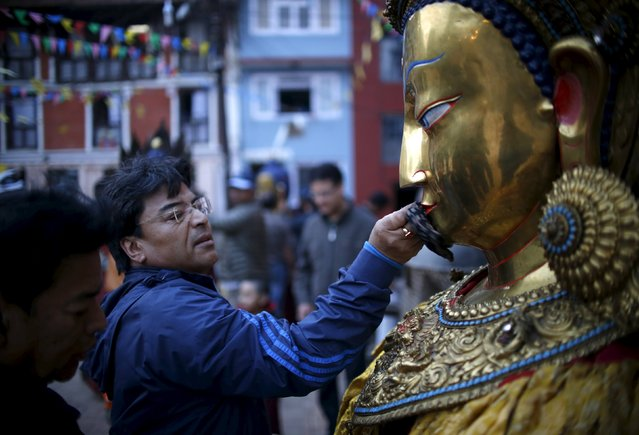 A devotee wipes an idol of Buddha during the Samyak festival in Lalitpur, Nepal, March 11, 2016. (Photo by Navesh Chitrakar/Reuters)