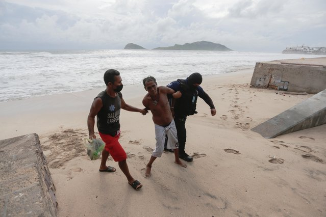 A police officer, with the help of a lifesaver, detains a man for refusing to leave a closed beach as storm Pamela approaches the Pacific coast resort, in Mazatlan, Mexico, October 12, 2021. (Photo by Daniel Becerril/Reuters)