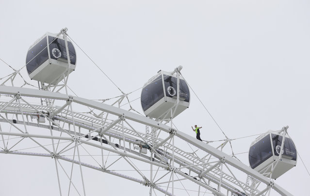 Daredevil performer Nik Wallenda walks untethered along the rim of the Orlando Eye, the city's new, 400-foot observation wheel, Wednesday, April 29, 2015, in Orlando, Fla. The walk is being done in advance of next month's public opening of the attraction. (Photo by John Raoux/AP Photo)