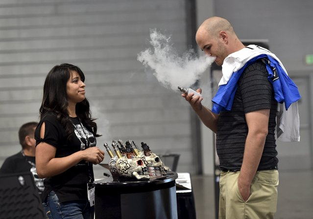 Jerred Marsh (R) samples flavored vape juice from Nancy Reyes at the Vape Summit 3 in Las Vegas, Nevada May 2, 2015. (Photo by David Becker/Reuters)