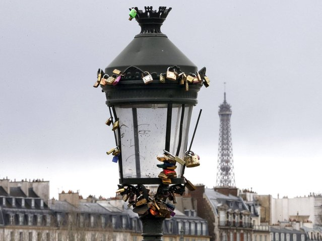 A view shows a street light covered with padlocks clipped by lovers on the Pont des Arts over the River Seine. (Photo by Charles Platiau/Reuters)