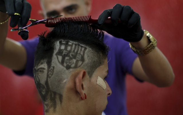 Hair artist and barber Nariko, 27, etches images of Barcelona's Neymar and his team's badge on the head of customer Luiz Fernadez, 15, before the Champions League semifinal first leg soccer match between Barcelona and Bayern Munich at his barbershop in Sao Vicente, near Santos, in Sao Paulo state May 6, 2015. (Photo by Nacho Doce/Reuters)