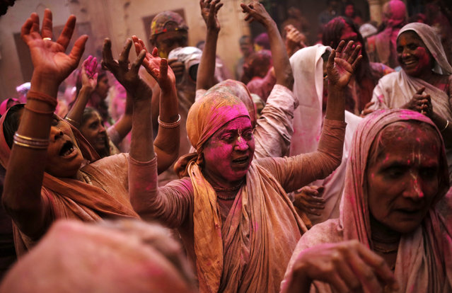 Widows daubed in colours dance as they take part in the Holi celebrations organised by non-governmental organisation Sulabh International at a temple at Vrindavan, in the northern state of Uttar Pradesh, India, March 21, 2016. (Photo by Anindito Mukherjee/Reuters)