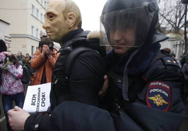 """Russian police officer detains an opposition activist in a mask depicting President Vladimir Putin and holding a poster, which reads """"Line Sentences to All"""" outside a court room in Moscow, Russia, Monday, February 24, 2014, where hearings started against opposition activists detained on May 6, 2012 during a rally at Bolotnaya Square. (Photo by Denis Tyrin/AP Photo)"""