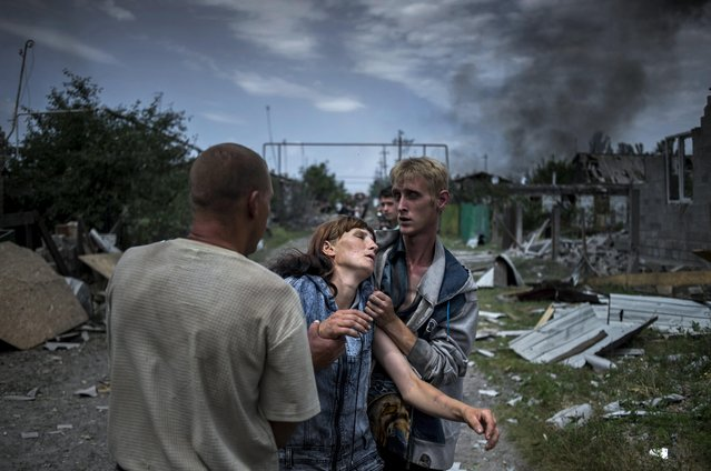 A handout photo made available by the World Press Photo (WPP) organization on 13 February 2017 shows a picture by Rossiya Segodnya photographer Valery Melnikov that won the Long-Term Projects – First Prize award of the 60th annual World Press Photo Contest, it was announced by the WPP Foundation in Amsterdam, The Netherlands on 13 February 2017. Caption: Citizens in the village of Luhanskaya after the air attack. Story: Ordinary people became victims of the conflict between self-proclaimed republics and the official Ukrainian authorities from 2014 onwards in the region of Donbass. Disaster came into their lives unexpectedly. These people were involved in the military confrontation against their will. They experienced the most terrible things: the death of their friends and relatives, destroyed homes and the ruined lives of thousands of people. (Photo by Valery Melnikov/EPA/Rossiya Segodnya/World Press Photo)