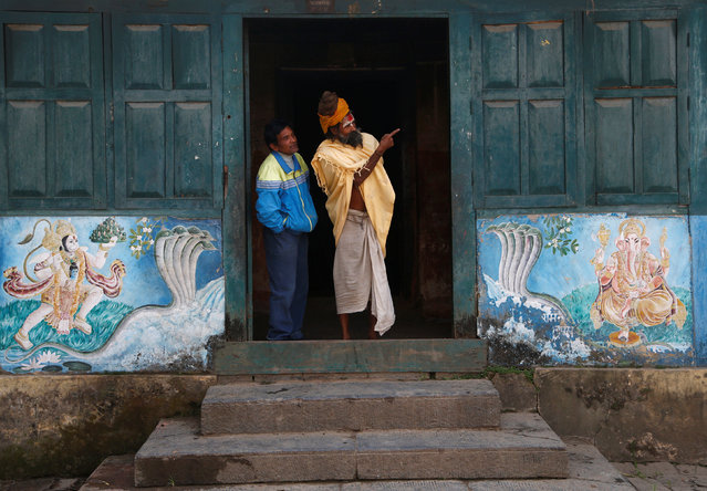 A Hindu holy man, or sadhu, speaks with a man as they stand on the doorway of an ashram at the premises of Pashupatinath Temple, ahead of the Shivaratri festival in Kathmandu, Nepal February 15, 2017. (Photo by Navesh Chitrakar/Reuters)