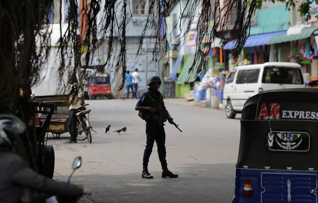 A Sri Lankan naval soldier stands guard at a road leading to a closed market on May Day in Colombo, Sri Lanka, Wednesday, May 1, 2019. Sri Lanka's major political parties called off traditional May Day rallies due to security concerns following the Easter bombings that killed more than 250 people and were claimed by militants linked to the Islamic State group. (Photo by Eranga Jayawardena/AP Photo)