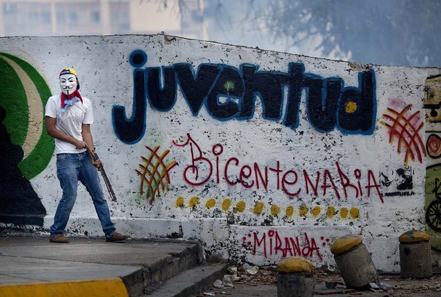 An anti-government protestor holds a piece of metal in Caracas, Venezuela, on February 22, 2014. After their opposition rally broke up in the late afternoon, in a pattern that has been seen in past demonstrations, about 1,000 stragglers erected barricades of trash and other debris and threw rocks and bottles at police and National Guardsmen. The troops responded with volleys of tear gas to prevent the students from reaching a highway and blocking traffic. (Photo by Rodrigo Abd/Associated Press)