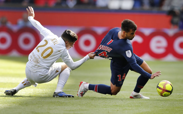 Nice's Youcef Atal, left, and PSG's Juan Bernat challenge for the ball during the French League One soccer match between Paris Saint-Germain and Nice at the Parc des Princes stadium in Paris, France, Saturday, May 4, 2019. (Photo by Christophe Ena/AP Photo)