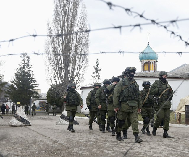 Uniformed men, believed to be Russian servicemen, march outside a Ukrainian military base in the village of Perevalnoye outside Simferopol, March 5, 2014. (Photo by Vasily Fedosenko/Reuters)