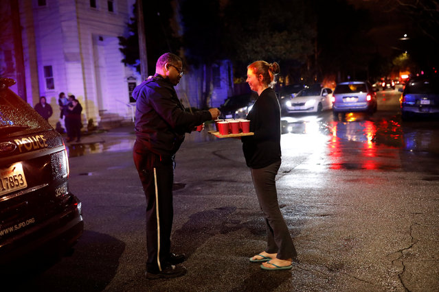 A resident gives a cup of hot tea to a police officer at a roadblock on South 20th Street along the flooded area near Coyote Creek in San Jose, California, U.S. February 21, 2017. (Photo by Stephen Lam/Reuters)