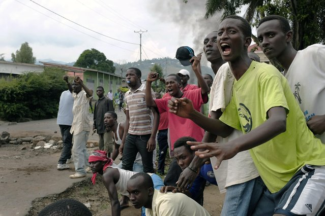 Demonstrators shout at police in the Musaga neighborhood of Bujumbura, Burundi, Wednesday May 20, 2015. Police returned to the neighborhood in full force Wednesday, firing live rounds and tear gas to disperse demonstrators protesting the president's decision to seek a third term. (Photo by Jerome Delay/AP Photo)