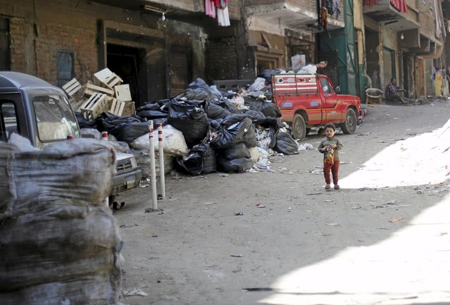 """A boy walks past rubbish in garbage dumps near a small recycling factory, in the shanty area known also as Zabaleen or """"Garbage City"""" on the Mokattam Hills in eastern Cairo, Egypt, April 4, 2016. (Photo by Amr Abdallah Dalsh/Reuters)"""