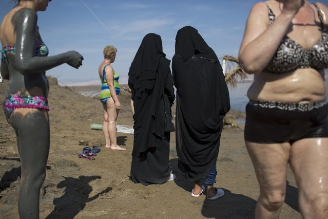 Two tourists from India visit the Dead Sea as others cover their bodies with mineral-rich mud, Israel, Friday, April 15, 2016. (Photo by Oded Balilty/AP Photo)