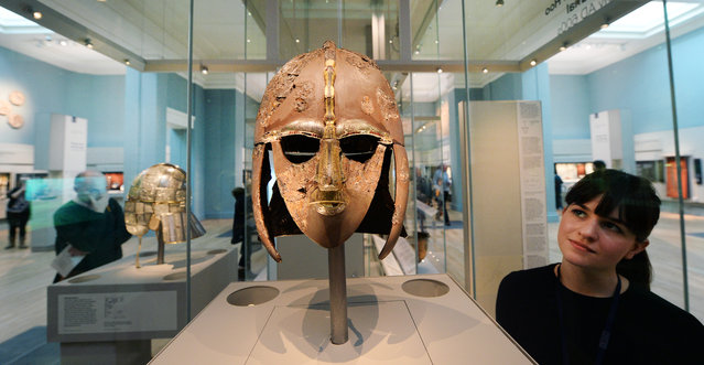 A woman looks at the Sutton Hoo helmet that is on display at the new public gallery in room 41 at the British Museum in London, Britain, March 25. 2014. The museum has opened a new gallery devoted to the archeological site of the Sutton Hoo treasure and Europe AD 300-1100 after undergoing a refurbishment.  (Photo by Andy Rain/EPA)