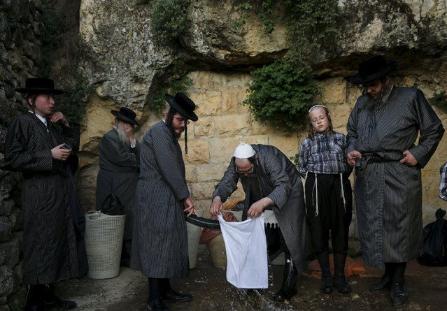 "Ultra-Orthodox Jews take part in the ""Mayim Shelanu"" ceremony to collect water from a natural spring, near Jerusalem April 21, 2016. The water is used to make matza, the traditional unleavened bread to be eaten on the Jewish holiday of Passover which starts on Friday. Passover commemorates the flight of Jews from ancient Egypt, as described in the Exodus chapter of the Bible. (Photo by Ronen Zvulun/Reuters)"