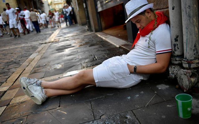A man sleeps as revellers walk at the street ahead of the running of the bulls at the San Fermin Festival, in Pamplona, northern Spain, Thursday, July, 11, 2019. Revellers from around the world flock to Pamplona every year to take part in the eight days of the running of the bulls. (Photo by Alvaro Barrientos/AP Photo)