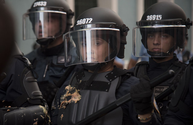 A police officer stands her ground after protesters threw food at officers, as police block them from reaching La Fortaleza governor's residence in San Juan, Puerto Rico, Sunday, July 14, 2019. (Photo by Carlos Giusti/AP Photo)