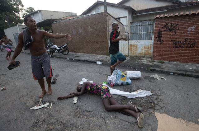 A woman affected by tear gas lies on the ground during an eviction in Rio de Janeiro, Brazil, Friday, April 11, 2014. Squatters in Rio de Janeiro are clashing with police after a Brazilian court ordered that 5,000 people be evicted from abandoned buildings of a telecommunications company. Officers have used tear gas and stun grenades to try to disperse the families. (Photo by Silvia Izquierdo/AP Photo)