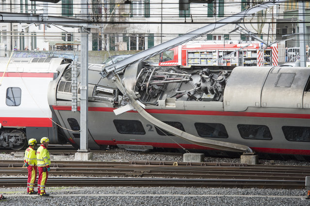 Rescuers stand next to a derailed train in the station of Lucerne, Switzerland, Wednesday, March 22,  2017. Swiss police say they are trying to reach people trapped inside the train in the  city of Lucerne, with details of any injuries still unclear. Rail company SBB says the Milan to Basel train derailed Wednesday as it was pulling out of Lucerne's main train station. (Photo by Urs Flueeler/Keystone via AP Photo)