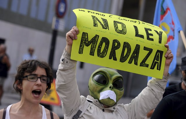 """A man wearing a mask with a tape over the mouth holds up a sign during a protest against the Spanish government's new security law in Gijon, northern Spain, June 30, 2015. The sign reads: """"Not to gag law"""". (Photo by Eloy Alonso/Reuters)"""