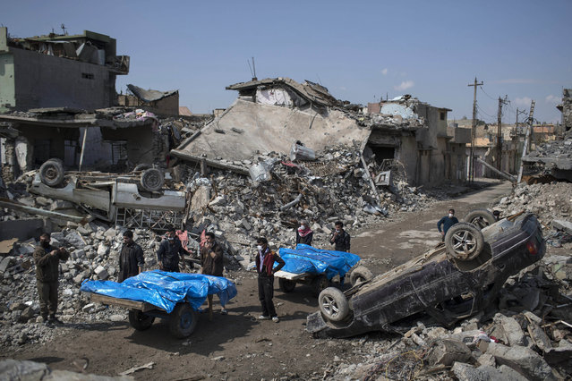 Residents carry the body of several people killed during fights between Iraq security forces and Islamic State on the western side of Mosul, Iraq, Friday, March 24, 2017. (Photo by Felipe Dana/AP Photo)