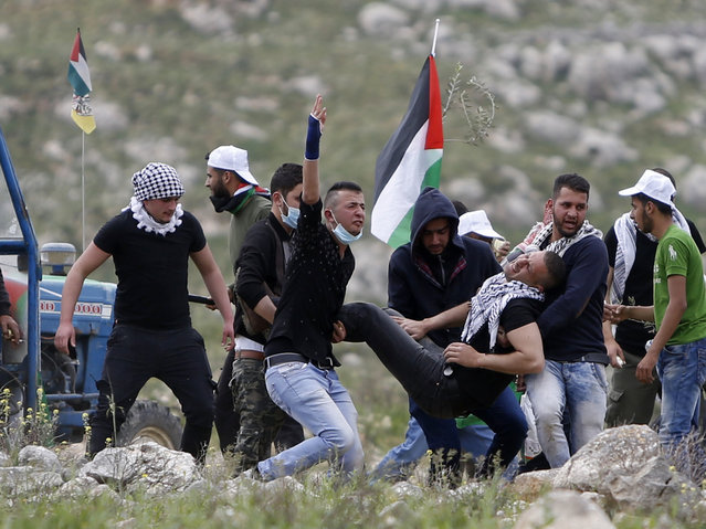 Palestinians carry injured demonstrator during clashes with Israeli forces following a protest to mark the Land Day near the village of Madama, south of the West Bank city of Nablus, Thursday, March 30, 2017. Land Day commemorates the killing of six Arab citizens of Israel by the Israeli army and police on March 30, 1976 during protests over Israeli confiscations of Arab land. (Photo by Majdi Mohammed/AP Photo)