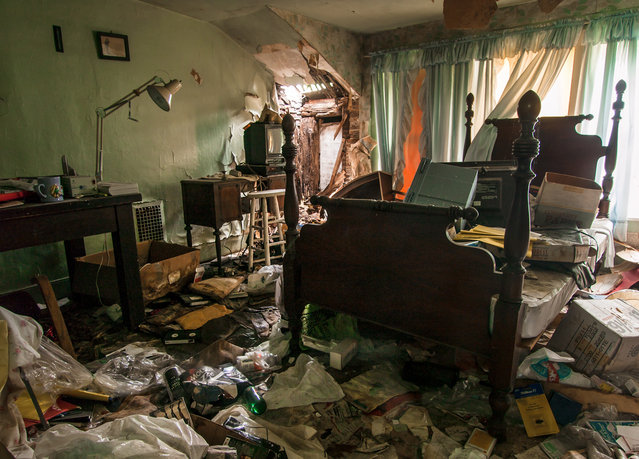 The remains of this house's former occupant, said to be navy man, lie scattered on the floor, Ohio. (Photo by Jonny Joo/Barcroft Media)