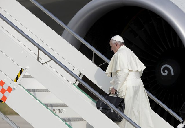 Pope Francis boards a plane for his pastoral trip, at Fiumicino airport in Rome, Italy, July 5, 2015. Pope Francis leaves for the trip to the continent of his birth, visiting Ecuador, Bolivia and Paraguay. The July 6-13 visit will include a visit to one of Latin America's most violent prisons when he will enter the notorious Palmasola prison in Santa Cruz, Bolivia, on July 10, his last day in the country. (Photo by Max Rossi/Reuters)