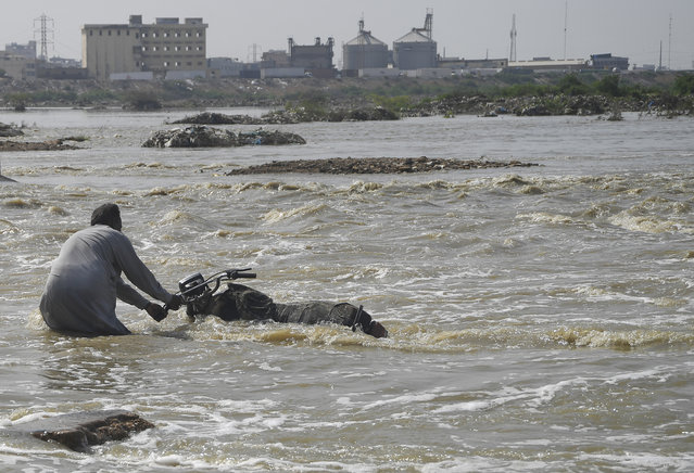 A Pakistani man tries to move his motorbike from a flooded street after heavy monsoon rains in the Pakistan's port city of Karachi on September 3, 2019. (Photo by Asif Hassan/AFP Photo)