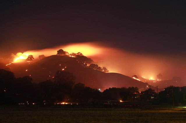 This 16-second time exposure shows a wildfire that might have been started by fireworks and burned more than 320 acres while threatening homes in the Northern California city of Vacaville, in the early morning hours of Sunday, July 5, 2015. The fire started Saturday night and embers were quickly spread by winds that gusted to 40 mph. Several homes were threatened and 125 people voluntarily evacuated, but no structures were burned. (Photo by Matthew Henderson/Vacaville Reporter via AP Photo)